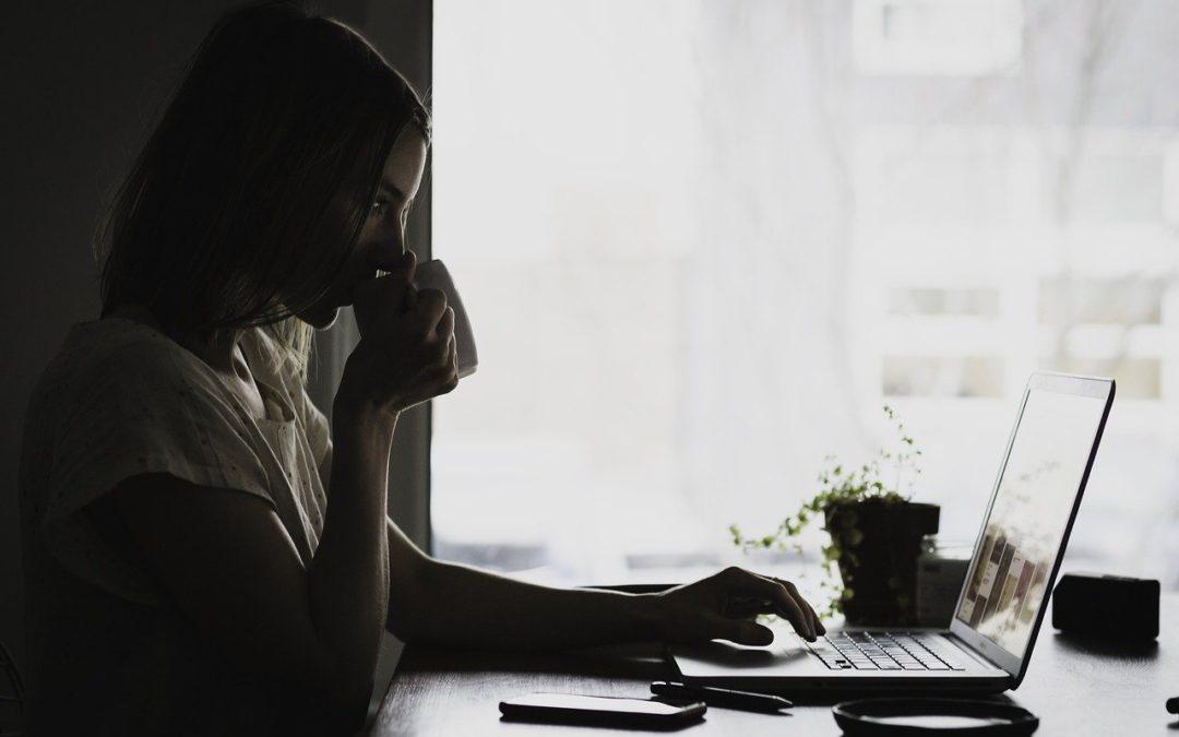 Passives Einkommen generieren - junge Frau mit Arbeitsmaterial und Laptop an einem Tisch